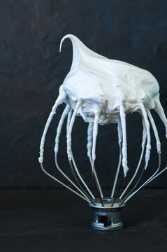 Whipped egg whites - beaten italian merengue on a whisk on black table,  closeup and copy space.