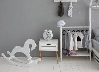 White wooden rocking horse in stylish modern children room.