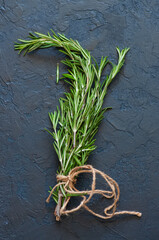 Close up of bunch of green fresh rosemary on a gray background. Copy space and top view.