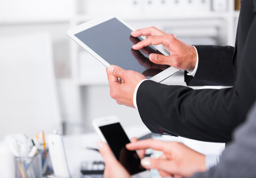 Hands of business partners using devices