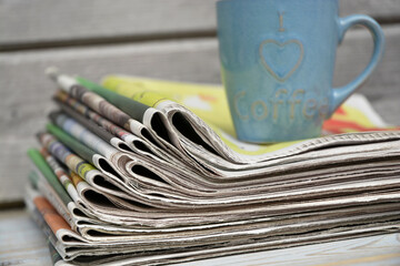 Stacked and piled up newspapers on a wooden table background