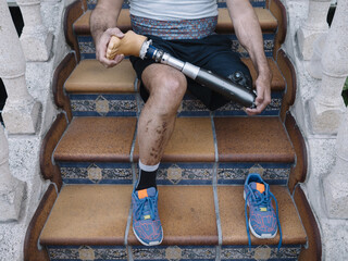 Low section of a disable man with prosthesis leg sitting on steps