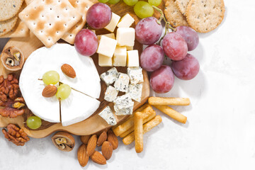 camembert, grapes and snacks on a white table, top view, closeup