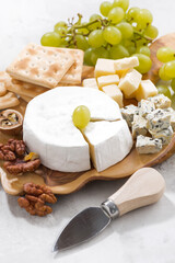 camembert, grapes and crackers on a white background, vertical, closeup