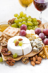 camembert, grapes, wine and snacks on a white table, vertical