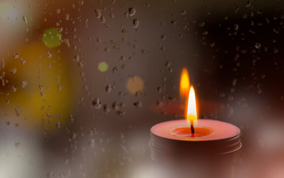 Vintage image of Light of Pink Candle in the front at window with blurred rain drops and low light nature background