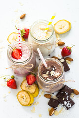 Banana chocolate and strawberry milkshakes in jars on white. Top view.