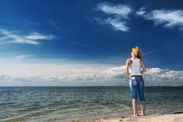 Young woman standing on sand and looking to a sky