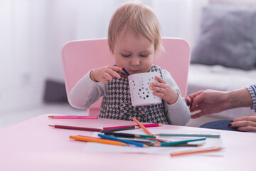 Blonde toddler girl drawing indoors while sitting on high chair