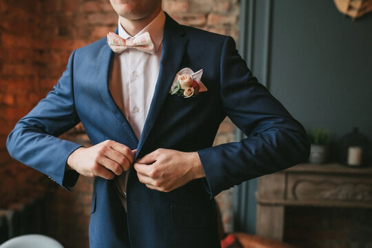 A young groom in a blue suit and a pink bow tie button his jacket against the backdrop of a brick wall and a fireplace