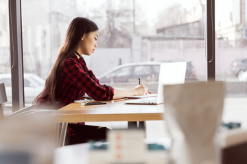 Serious young woman using laptop and taking notes at coffee break