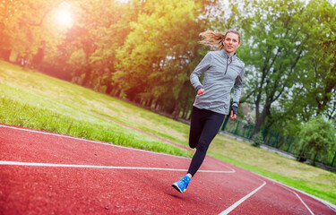 Athletic woman running on track, healthy lifestyle