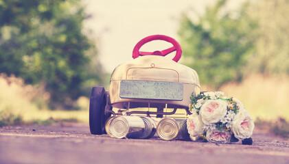 Hochzeitsreise, Brautstrauß und Blechdosen am Auto
