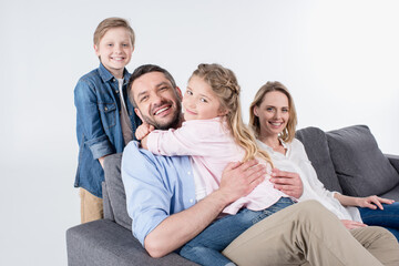 caucasian family looking at camera while sitting on sofa together isolated on white