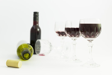 Concept of alcohol consumption, alcoholism and abuse with a line of beautiful crystal glasses filled with red wine, a full and an empty bottle. Stages of drinking underlined by blurred image effect.