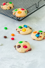 Cookies with colorful candies and chocolate chips on a white stone background.