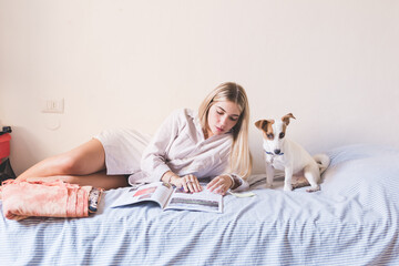 woman young lying bed with dog reading