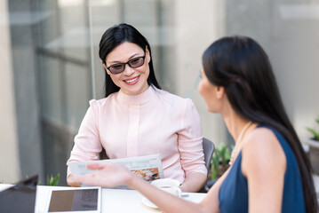 Cheerful woman telling with colleague
