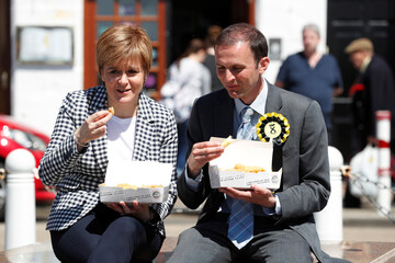 Scotland's first Minister and SNP leader Nicola Sturgeon eats fish and chips with local candidate Stephen Gethins outside a fish bar in Anstruther, Scotland