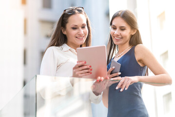 Beaming females watching at electronic tablet