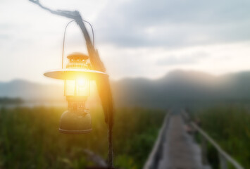 focus on the lantern amb which hang over the bamboo path way alongside papyrus to the lake with mountain view with fake lighting