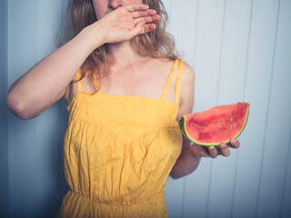 Woman wiping face after eating water melon