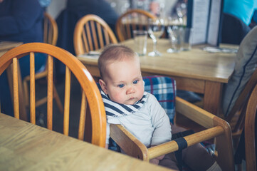 Cute little baby sitting at table in restaurant