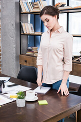 Serious young businesswoman with pen standing at table and writing in notebook