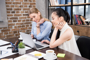 smiling multicultural businesswomen working with laptop and sitting at workplace