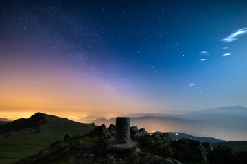 The wonderful starry sky over Torino (Turin, Italy) from the majestic mountain range of the Italian Alps, with glowing lights of the valley below.
