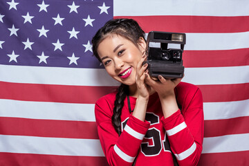 smiling asian woman holding retro photo camera with american flag behind