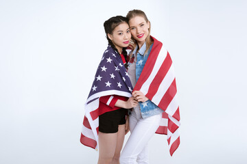 young multiethnic girls standing together and looking at camera with flag of USA, Independence Day Celebration