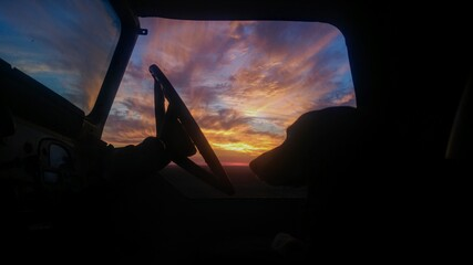 Silhouette of a dog and steering wheel before a stunning sunset in open country.