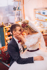 Bride in beautiful dress and groom in black suit sitting on sofa indoors in white studio interior like at home. Trendy wedding style. Groom.bride hugging