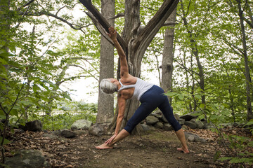 Mature woman doing yoga in forest