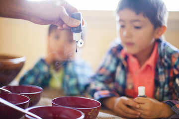 A mother adds organic Natural food coloring dye to bowls of hot water to color Organic Easter Egg. Her two sons, a four year old and seven year old eagerly await to begin the dying (coloring) process.