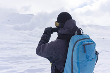 A snowboarder taking a picture on his phone of the fume holes on Mt. Asahi