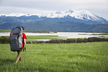 Young male hikes through grassy field towards a lake with an inflatable paddleboard in the mountains