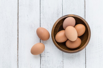 eggs in a wooden bowl on old wooden table top view
