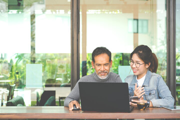 Smiling Attractive mature man with white stylish short beard using tablet with charming woman teenage. Serving internet via his gadget. Teaching old man using social network technology