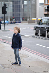 The child is in a city street. London, Great Britain.