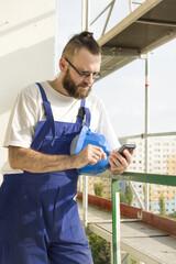 Pracownik budowlany w stroju roboczym trzyma w ręku kask budowlany, telefon komórkowy i wybiera numer. Praca na dużej wysokości. Rusztowania w tle.