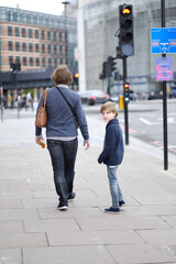 A man with a child on a city street. London, Great Britain.