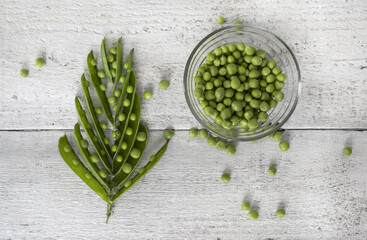 Green peas, freshly picked, arranged on wooden background. Top view