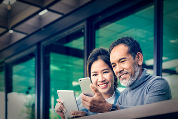 Smiling Attractive mature man with white stylish short beard using smartphone with charming woman teenage. Serving internet via his gadget. Teaching old man using social network technology