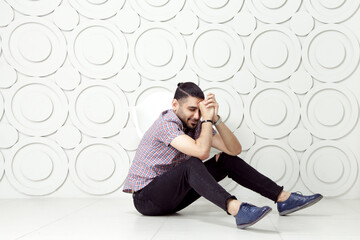 Young bearded fashion model in casual style is posing near white circle wall background. studio shot. sitting on floor and smiling with closed eyes.