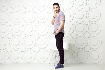 Young bearded fashion model in casual style is posing near white circle wall background. studio shot. looking at camera with smile.
