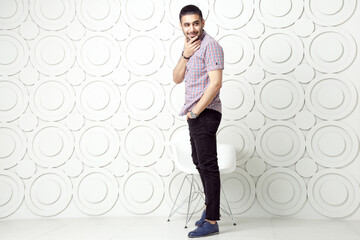 Young bearded fashion model in casual style is posing near white circle wall background. studio shot. smiling and looking away with hand on packet.