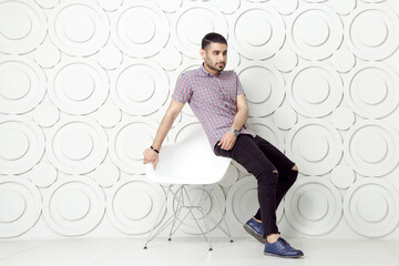 Young bearded fashion model in casual style is posing near white circle wall background. studio shot. sitting on chair and looking at away.