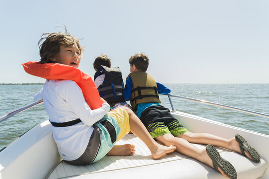 Boys wearing life jackets traveling in boat